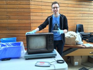 A student smiles and points to an old television set.