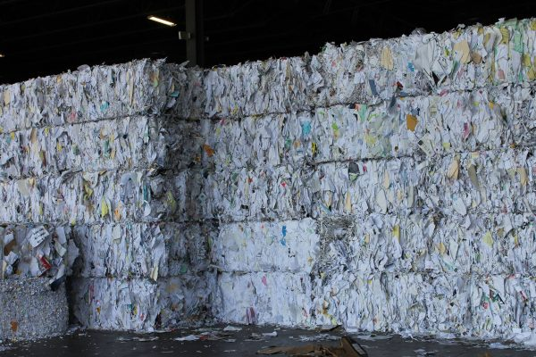 A recycling site filled with compressed blocks of paper and recyclables.