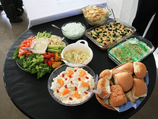 Photo of food - veggie platter, buns, chips, casserole, sauces, pasta, and more.