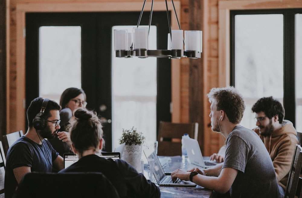 Photo of a group of 5 people working indoors around a table.