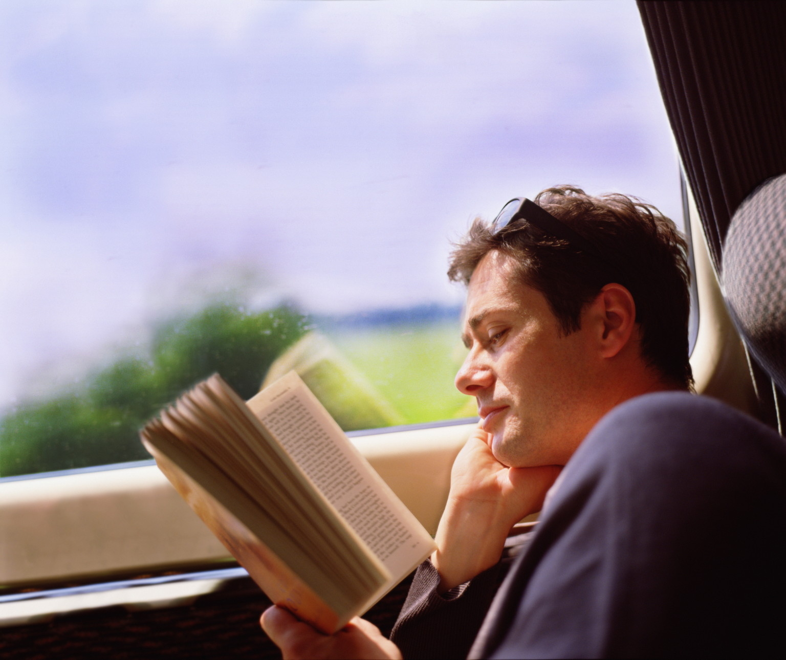Photo of a man on a train, reading a book.