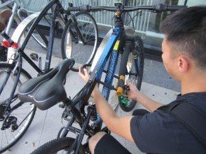 Photo of a man securing his bike using a bike lock.