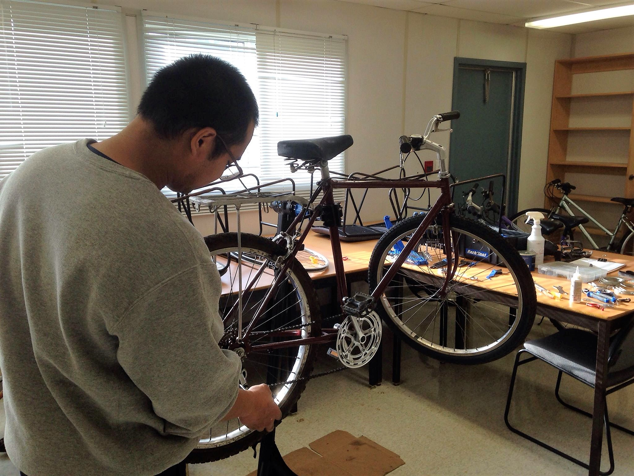 A man inspects his bike, checking the wheel and chain.